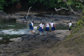A group of girls helping one another to cross the river in search of more trash.